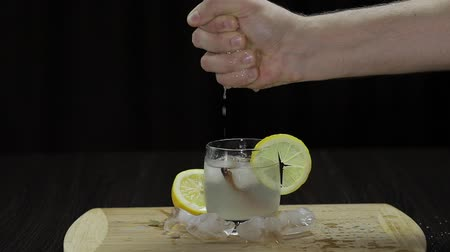 wódka : Squeezing lemon juice into a glass. Fornt view.