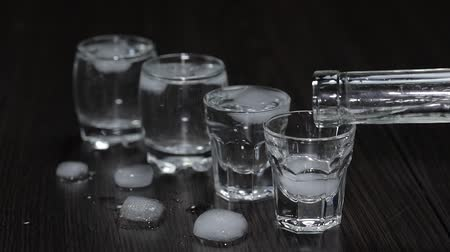 ice cube : Pour vodka from a bottle into shot glasses with ice cubes.