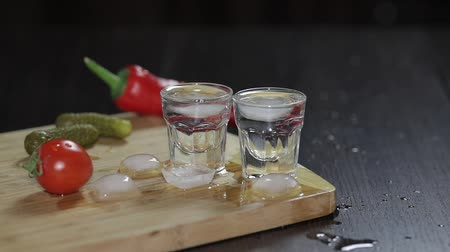 ginástico : Vodka in shot glasses on rustic wood board. Adding ice cubes Stock Footage