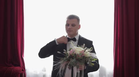 smokin : Handsome groom standing near window with a bunch of wedding flowers. Wedding bouquet. Business man. Slow motion