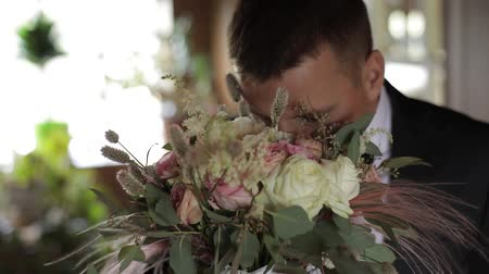 red tie : Handsome groom standing near window with a bunch of wedding flowers. Wedding bouquet. Business man. Slow motion