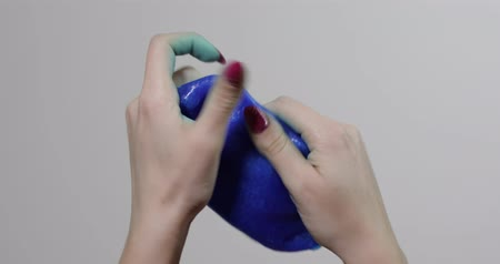 gumka : Woman hands playing with oddly satisfying blue slime sticky gooey substance on white background. Super viral trend on social media for those little things that are inexplicably satisfying. Antistress