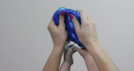 goop : Woman and child hands playing with oddly satisfying blue slime sticky gooey substance on white background. Super viral trend on social media for those little things that are inexplicably satisfying