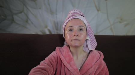 tv channel : Beautiful cheerful woman sitting on the sofa at home and watching a late night movie at TV, relaxing, eating popcorn. In a bathrobe with a towel on her head, the face is covered by facial mask