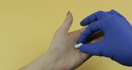 fragilidade : Doctor hand dressed in rubber blue sterile medical glove puts one oval white pill into woman hand. Concept of medicine and health improvement. Disease and the way of its treatment Vídeos