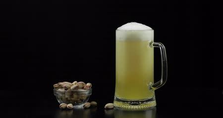 quartilho : Beer is pouring into glass on black background. Bowl of pistachios nuts.
