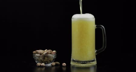pint glass : Beer is pouring into glass on black background. Bowl of pistachios nuts.