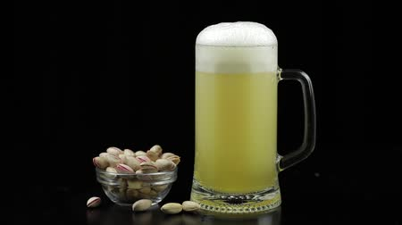 harmatcsepp : Beer is pouring into glass on black background. Bowl of pistachios nuts. Slow motion