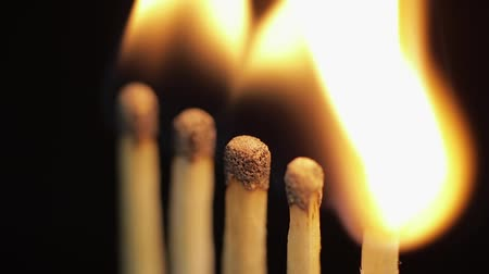 fade in : Matches light up one by another in series on black background. Slow motion and time lapse Stock Footage