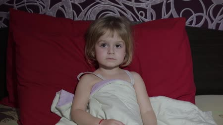 передавать : Young girl watching tv television on the bed. Kid hypnotized by screen watching content. Child in hypnosis state
