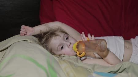transmitir : Young girl watching tv television on the bed and drinks a juice from a bottle. Kid hypnotized by screen watching content. Child in hypnosis state Vídeos