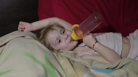 передавать : Young girl watching tv television on the bed and drinks a juice from a bottle. Kid hypnotized by screen watching content. Child in hypnosis state Стоковые видеозаписи