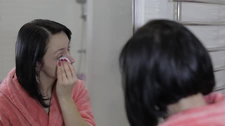 algodão : Beautiful brunette woman using cotton pads. Woman removing makeup in front of mirror in bathroom. Beauty Skin care concept. Close up