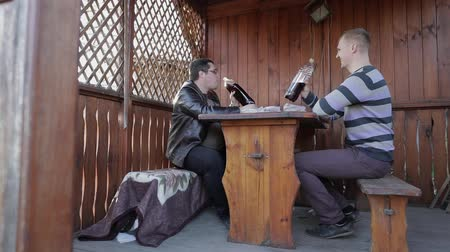 harcerz : Two men sit at the table on terrace and drink beer from plastic bottles. Happy and satisfied.