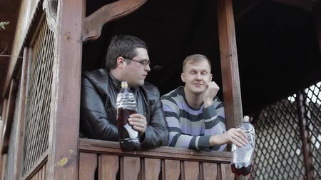 harcerz : Two men on terrace drink beer from plastic bottles and speaking. Happy and satisfied. Wideo