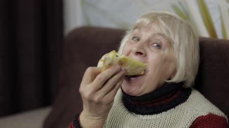 представитель старшего поколения : Beautiful elderly woman is sitting on sofa and eats pizza. Smiles and shows how tasty the pizza is. Grandmother looks very nice Стоковые видеозаписи