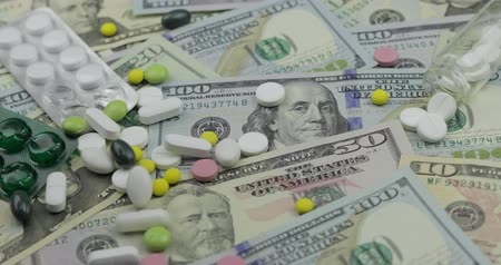 finansman : Pills falling on dollar banknotes, expensive medication, pharmaceutical business. Investment in hospitals, high price treatment, medical consumerism. Drugs development and production, market financing