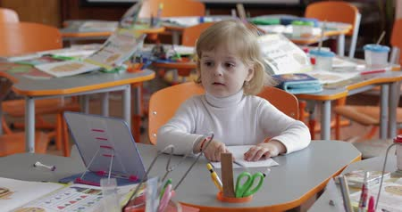 spolužák : Girl drawing at the table in classroom. Education process. Happy three years old child sitting at a desk. Cute girl smiling Dostupné videozáznamy