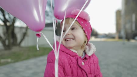 balões : Happy cute child at the street with multicolored balloons with helium. Baby holding a baloons in hand. Concept of happy childhood. Going to birthday party. Slow motion Stock Footage