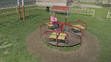 детский сад : Funny cute girl is playing on schoolyard. Joyous female child having fun on playground sittinig on carousel. Slow motion
