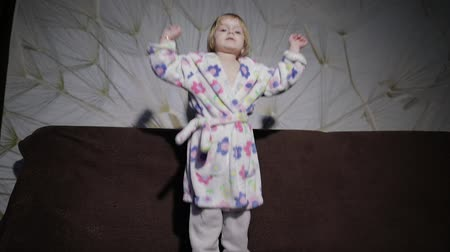 śpiew : Little cute girl with blond hair jumps on sofa. Bathrobe clothes. Feels happy. Slow motion