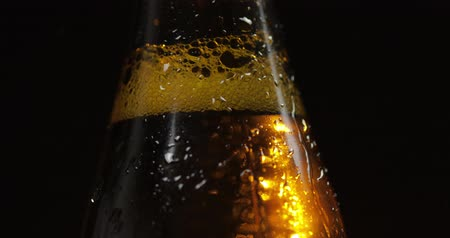 condensa : A bottle of cold beer on a black background. A ray of light beautifully illuminates it, it slowly rotates. Craft light beer in bottle with condensate and water drops. Close-up shot Filmati Stock