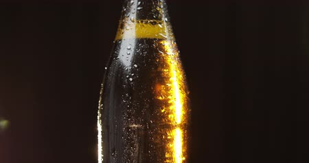 condensa : A bottle of cold beer on a black background. A ray of light beautifully illuminates it, it slowly rotates. Craft light beer in bottle with condensate and water drops Filmati Stock