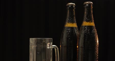 pisztácia : Two bottle of cold beer on a black background. A ray of light beautifully illuminates them. Empty drinking glass and pistachio nuts. Craft light beer in bottles. Camera slowly panning Stock mozgókép