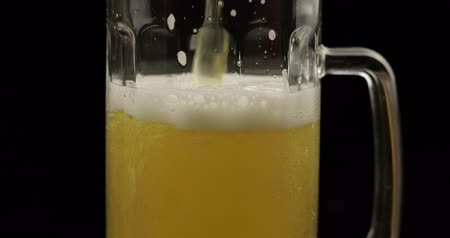 ale : Pouring cold golden light beer into a glass. Craft beer making bubbles and foam. Close-up shot. Black background