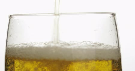 karczma : Pouring cold golden light beer into a glass. Craft beer making bubbles and foam. Close-up shot. White background