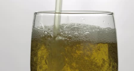 quartilho : Pouring cold golden light beer into a glass. Craft beer making bubbles and foam. Close-up shot. White background
