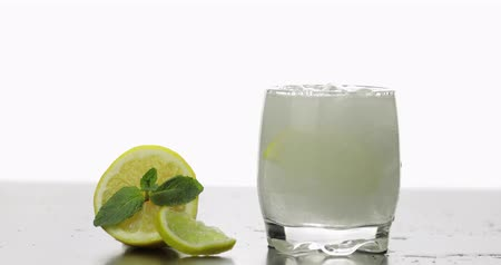 tonik : In a glass pour a cold drink with leaves of mint, lime, lemon and ice cubes. Releasing bubbles and foaming in sparkling water. Aerated water In glass on white background. Making cocktail