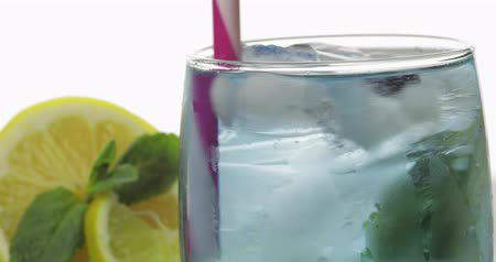 смородина : Stiring in a glass with cold drink, leaves of mint, lime, lemon, black currants and ice cubes. Releasing bubbles and foaming in sparkling water. Drink in glass on white background. Making cocktail