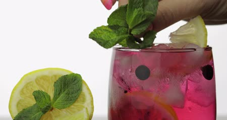 красная смородина : Adding leaves of mint in a glass with cold drink, lime, lemon, black currants and ice cubes. Releasing bubbles and foaming in sparkling water. Drink in glass on white background. Making red cocktail