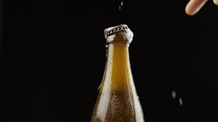 craft beer : Opening cold bottle of beer with bottle opener. Cold beer on a black background. Craft light beer in bottle with condensate and water drops. Close-up shot. Slow motion
