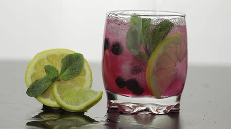 красная смородина : Pour water in a glass with leaves of mint, lime, lemon, black currants and ice cubes. Releasing bubbles and foaming in sparkling water. Drink in glass on white background. Making red cocktail