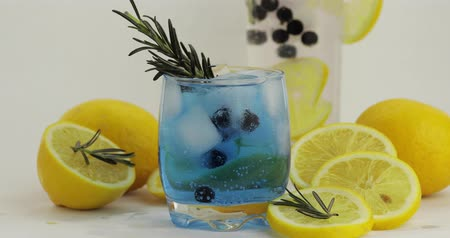 смородина : Adding lemon slice and rosemary branch in a drinking glass with cold drink. Making refreshing soda lemonade blue cocktail with lemon, ice cubes and black currant. Tonic fizzy water with bubbles