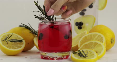 красная смородина : Adding rosemary branch in a drinking glass with cold drink. Making refreshing soda lemonade red cocktail with lemon, ice cubes and black currant. Tonic fizzy water with bubbles. White background Стоковые видеозаписи