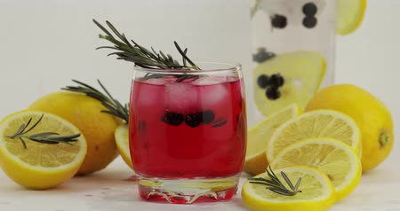 красная смородина : Adding rosemary branch, lemon slice, drinking straw in a drinking glass with cold drink. Making refreshing soda lemonade red cocktail with lemon, ice cubes and black currant. Tonic water with bubbles