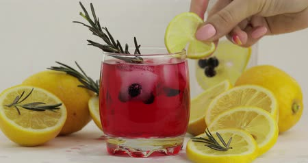 смородина : Adding rosemary branch, lemon slice, drinking straw in a drinking glass with cold drink. Making refreshing soda lemonade red cocktail with lemon, ice cubes and black currant. Tonic water with bubbles