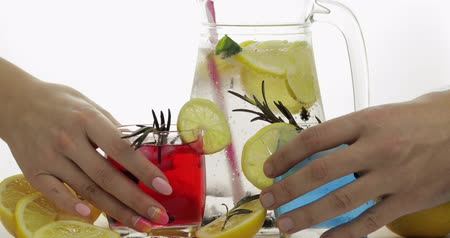 clear liquid : Woman and man hands takes refreshing soda lemonade red and blue cocktails with lemon, ice cubes and black currant in a drinking glass. Tonic fizzy water with bubbles. White background Stock Footage