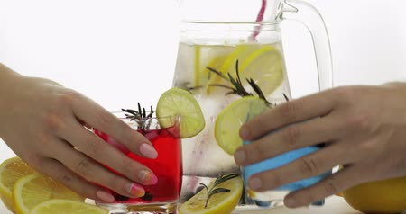 tonik : Woman and man hands takes refreshing soda lemonade red and blue cocktails with lemon, ice cubes and black currant in a drinking glass. Tonic fizzy water with bubbles. White background Stok Video