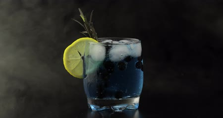 tonik : Adding black currants in a drinking glass with cold drink. Making refreshing soda lemonade blue cocktail with lemon and ice cubes. Tonic fizzy water with bubbles. Black background Stok Video