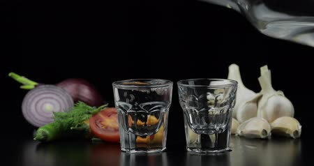 wódka : Pouring up shot of vodka from a bottle into two glass with onion, hot pepper, cherry tomato, dill and garlic against black background. Pour of alcohol drink