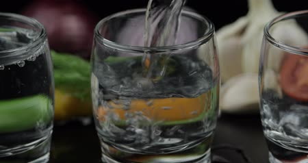 cold drinks : Pouring up shots of vodka from a bottle into three glass with onion, hot pepper, cherry tomato, dill and garlic against black background. Pour of alcohol drink. Close-up shot Stock Footage