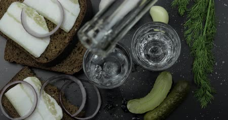 укроп : Pouring up shot of vodka from a bottle into two glass. Bread with lard, onion, dill, pickled cucumbers and garlic on black surface. Pour of alcohol drink. View from top