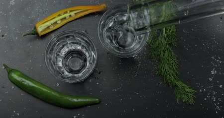 chili : Pouring up shot of vodka from a bottle into two glass. Hot pepper and dill on black surface. Pour of alcohol drink. View from top