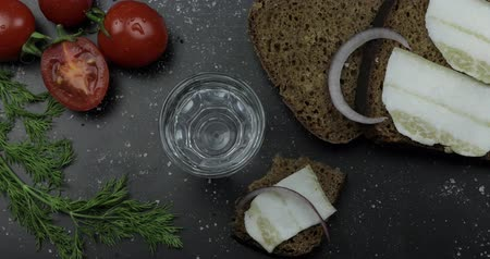 tomates cereja : Pouring up shot of vodka from a bottle into glass. Bread with lard, onion, dill and cherry tomatoes on black surface. Pour of alcohol drink. View from top