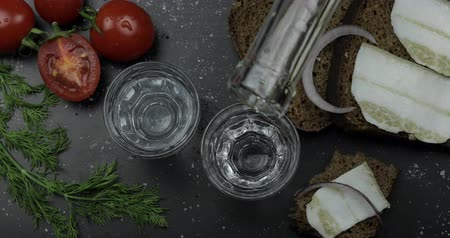 укроп : Pouring up shot of vodka from a bottle into two glass. Bread with lard, onion, dill and cherry tomatoes on black surface. Pour of alcohol drink. View from top