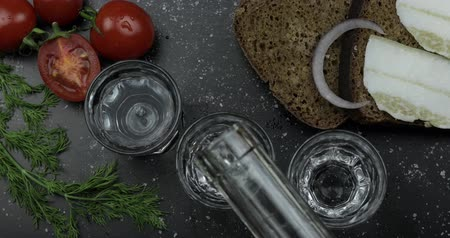 bekap : Pouring up shot of vodka from a bottle into three glass. Bread with lard, onion, dill and cherry tomatoes on black surface. Pour of alcohol drink. View from top